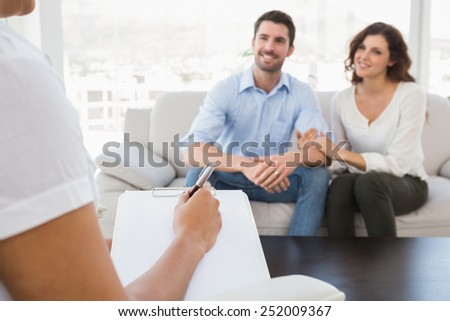Reconciled couple smiling and talking with their therapist in the office - stock photo