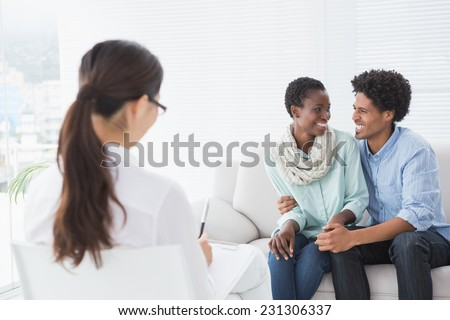 Reconciled couple smiling at each other in therapists office - stock photo