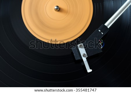 Record player stylus on a rotating disc with orange label - stock photo