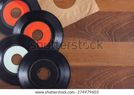 Record vinyl top view in wooden background - stock photo