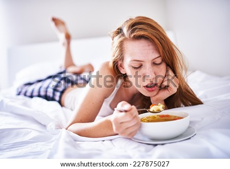 recovering woman in bed eating chicken soup while sick - stock photo