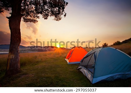 recreation area and camp with tent, sunset time with rising sun near high mountain lake  - stock photo