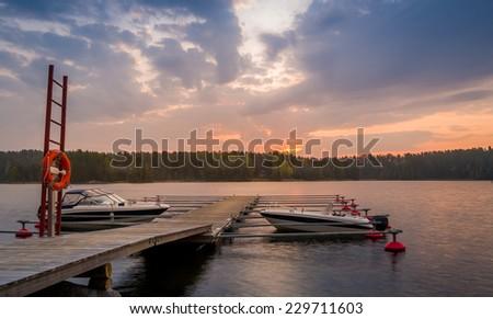 Recreational boats docked at wooden pier. Romantic sunset scene. - stock photo