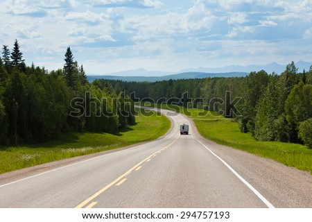 Recreational Vehicle RV on empty road of Alaska Highway, Alcan, in boreal forest taiga landscape south of Fort Nelson, British Columbia, Canada - stock photo