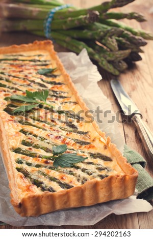 Rectangle-shaped grilled asparagus savory tart with pecorino and bacon next to a french cutting knife on a rustic wooden background. Retro stule toned. - stock photo