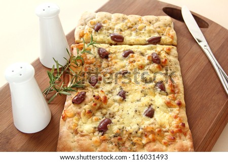 Rectangular gourmet pizza with cheese and olives ready to serve. - stock photo