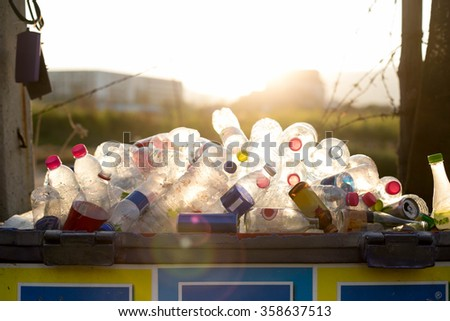 Recyclable garbage of glass and plastic bottles in rubbish bin - stock photo