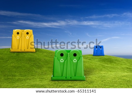 Recycle containers for glass, metal, plastic and paper waste placed on a green meadow lansdscape - stock photo
