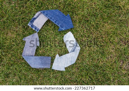 Recycle Logo from used old denim fabric on green grass background - stock photo