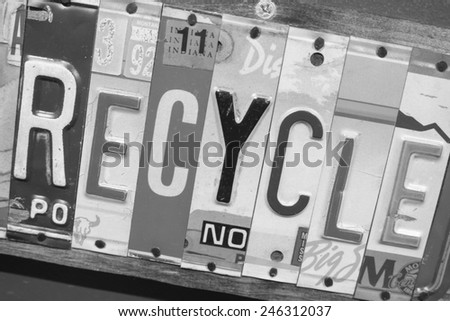 Recycle sign made out of state license plates.  Each letter, spelling the word recycle, is a piece of a state license plate - stock photo
