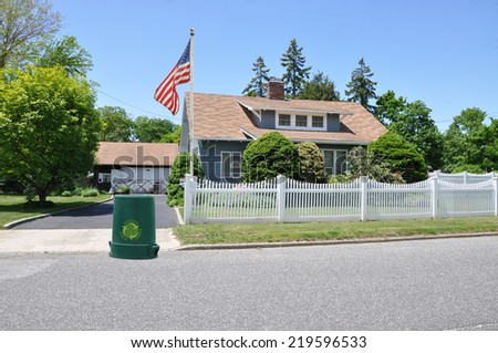 Recycle trash Can American Flag Pole Suburban cape cod style home with white picket fence residential neighborhood clear blue sky USA - stock photo