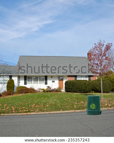 Recycle trash container on street in front of suburban bungalow style home autumn season residential neighborhood blue sky clouds USA - stock photo