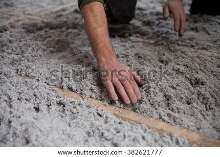 Recycled paper insulation -  help green energy use recycled materials in new architecture and diy. Man's hands putting isolation to the wooden frames under the floor - stock photo