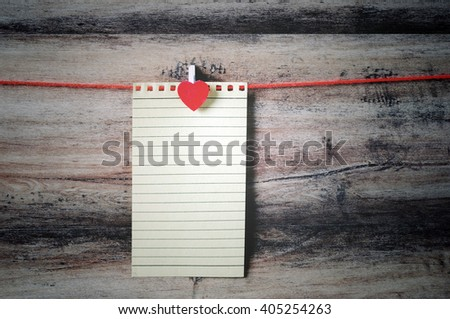 Recycled paper with clothespin hanging on a string with wooden background, retro style. - stock photo