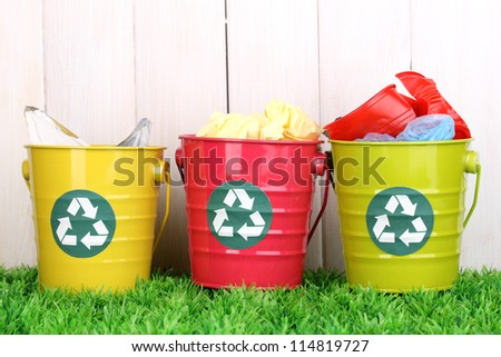 Recycling bins on green grass near wooden fence - stock photo