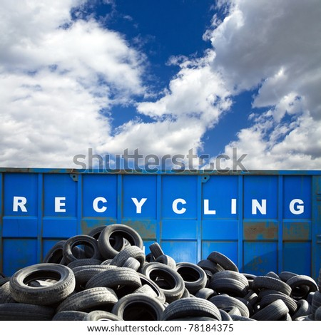 Recycling container and car tires over blue sky, business and ecology - stock photo