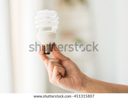 recycling, electricity, environment and ecology concept - close up of hand holding energy saving lightbulb or lamp - stock photo