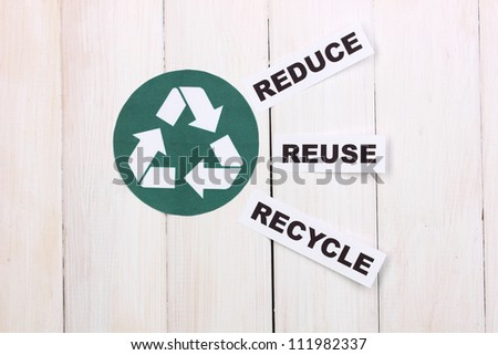 Recycling sign on wooden background - stock photo