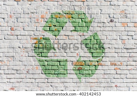 Recycling symbol on white stone wall background. Concept of environment, reuse and green lifestyle. - stock photo
