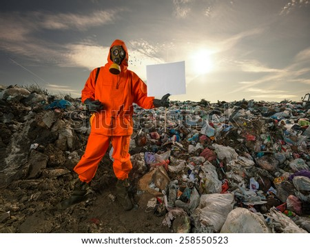 Recycling worker standing on the landfill and holding blank cardboard sign. - stock photo