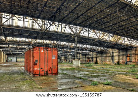Red abandoned container in a derelict warehouse - stock photo