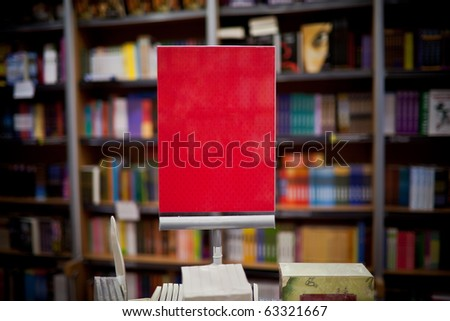 Red ad space in bookstore - many books in the background - stock photo