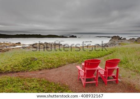 Red Adirondack Chairs overlooking coastal landscape of Newfoundland, NL, Canada - stock photo