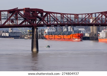 Red adjustable lifting iron truss bridge Rose Portland Willamette River through which float on large small ships boats background of port where large ships large red dry cargo ship for loading cargo - stock photo