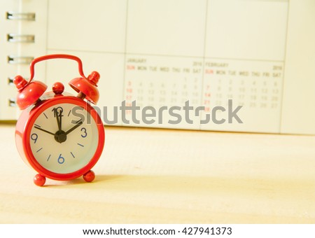 Red alarm clock and on calendar background - stock photo