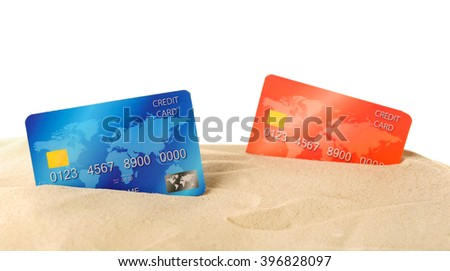 Red and blue bank cards in sand isolated on white - stock photo