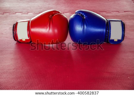 Red And Blue boxing gloves On Red rubber flooring - stock photo