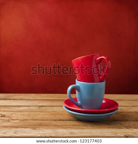 Red and blue coffee cups on wooden table over red grunge wall - stock photo