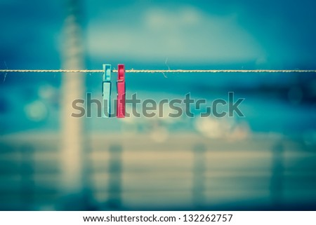 red and blue colored clothespins on rope - stock photo