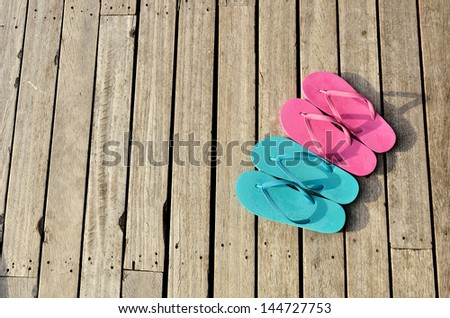 Red and blue flip-flops on the wooden floor  - stock photo