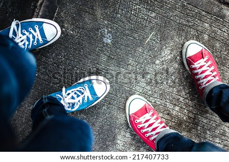 Red and Blue Sneakers shoes walking on Dirty concrete top view , Canvas shoes walking on concrete , two sneakers behind each others as a sign of love , Sneakers shoes Couple - stock photo