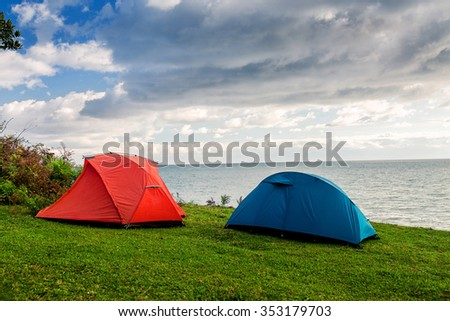 Red and blue tents are set on the grass by the sea - stock photo