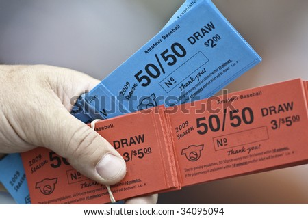 Red and blue tickets for a 50/50 draw.Partial hand and fingers hold the tickets, - stock photo
