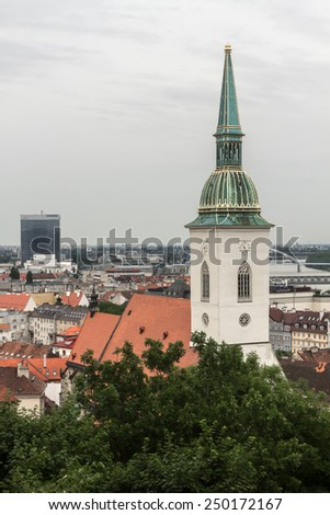 Red and brown tiled roofs, the main clock tower of the city of Bratislava in Slovakia. Summer view of the city from the mountains. Green trees and cloudy sky - stock photo