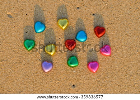 Red and colorful chocolate hearts candies on beach sunset - stock photo