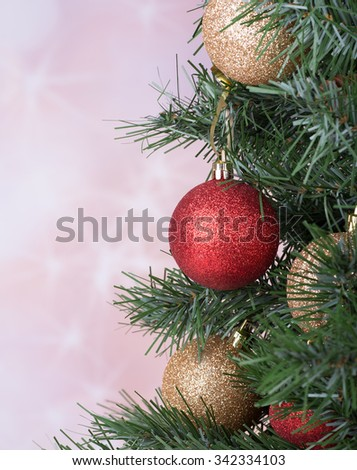 Red and gold baubles on a Christmas tree with a holiday background - stock photo