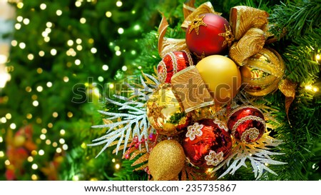 Red and gold Christmas balls hanging on green pine tree, close up - stock photo