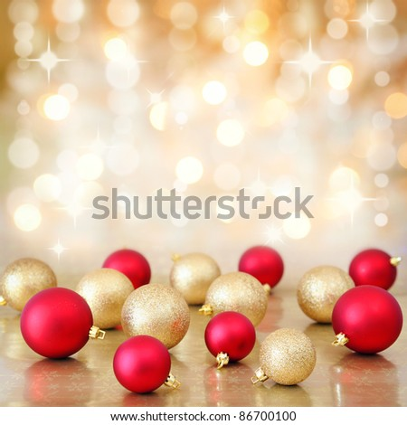Red and gold Christmas baubles ornaments on background of defocused golden lights. Shallow DOF. - stock photo