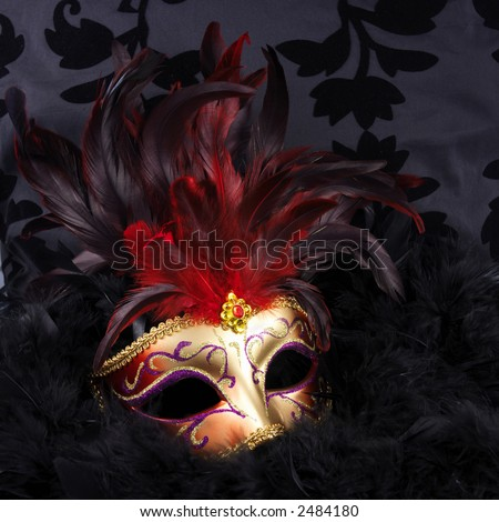 Red and golden mask with black feathers (Venice) on a black velvet background - stock photo
