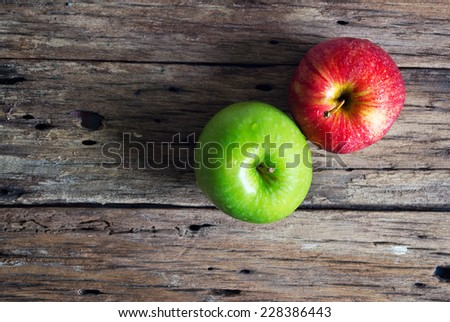 Red and green apple on old wooden table  - stock photo