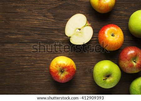 Red and green apples on wooden background. - stock photo