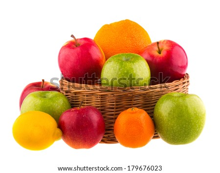Red and green apples, oranges and lemons in a wooden basket, isolated on white background. - stock photo