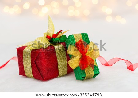 Red and green Christmas gift box with shiny ribbon. Bokeh with glow effect on white background - stock photo