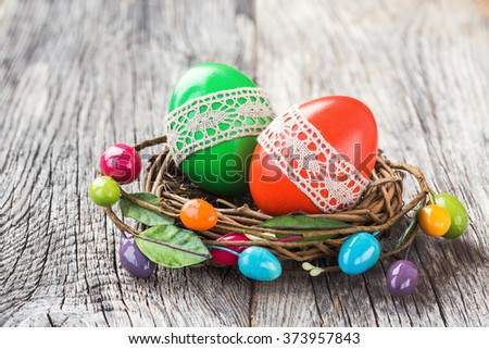 Red and green Easter eggs decorated with lace in small decorative nest. Selective focus - stock photo