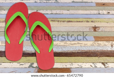red and green flip flop sandals on old painting wood - stock photo