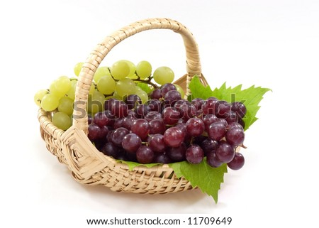 Red and Green grapes in a Basket on a bright background - stock photo